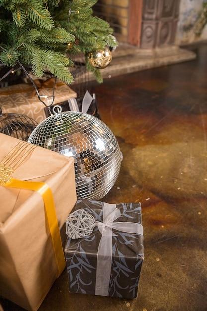 Крупный план елки, украшенной золотыми шарами. под елкой большое количество Premium Фотографии