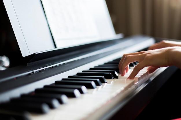 Крупный план руки исполнителя классической музыки, играющей на пианино или электронном синтезаторе (фортепианной клавиатуре), размытый фон Premium Фотографии