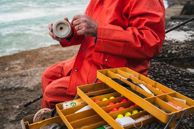釣り道具箱と餌を入れて漁師のクローズアップ。釣りとスポーツのコンセプトです。 無料写真