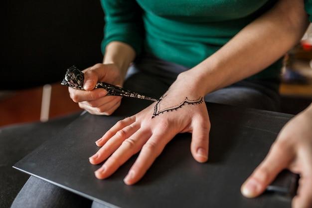 Крупный план девушки, рисование heena над рукой женщины Бесплатные Фотографии