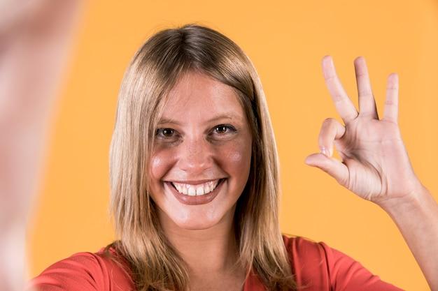 Конец-вверх счастливой женщины показывая о'кеы жест на предпосылке студии Бесплатные Фотографии
