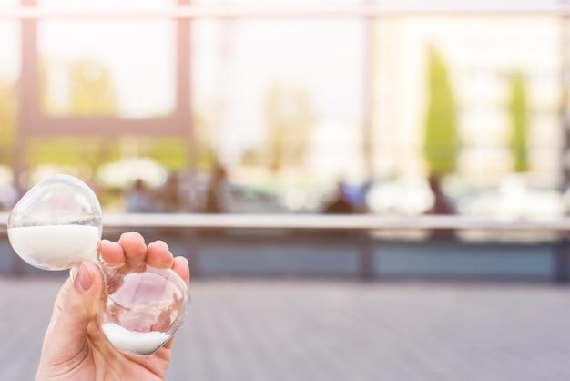 砂時計を屋外に持っている人間の手のクローズアップ Premium写真