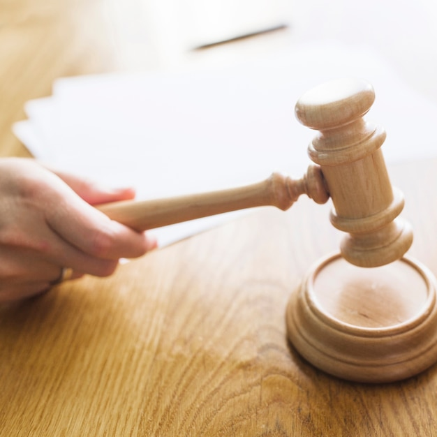 Close Up Of A Judges Hand Striking Gavel On Sounding Block Free Photo