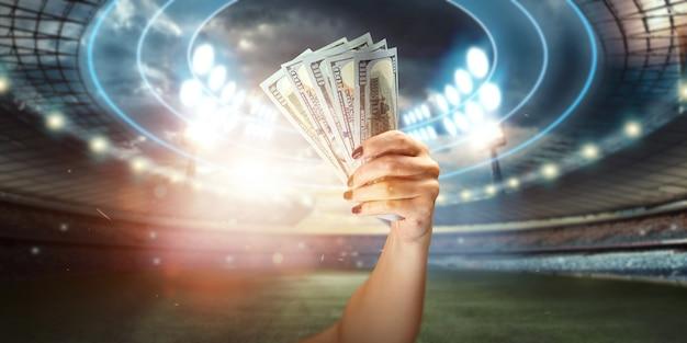 スタジアムの背景に米ドルを持っている男の手のクローズアップ。スポーツくじ、賭け、ギャンブルから利益を得るという概念。アメリカンフットボール。 Premium写真