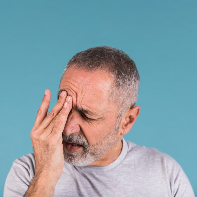 Крупный план зрелого человека, страдающего от головной боли на синем фоне Premium Фотографии