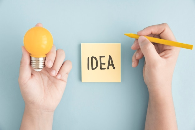 Close Up Of A Person Holding Yellow Crayon And Light Bulb With Idea Text On