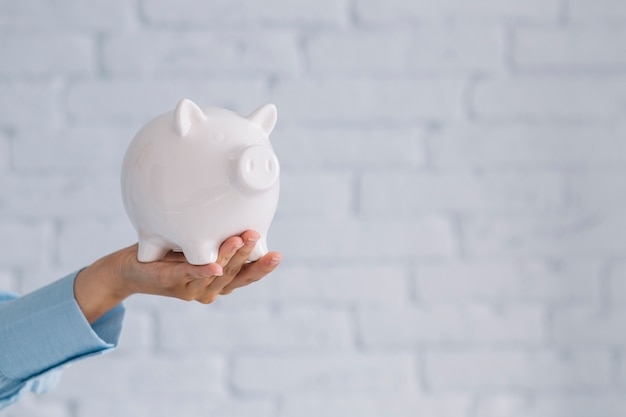 Close-up of a person's hand holding white piggybank Free Photo