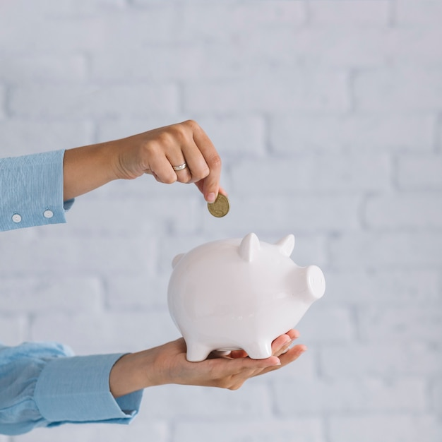 Close-up of a person's hand inserting coin in white piggybank Free Photo