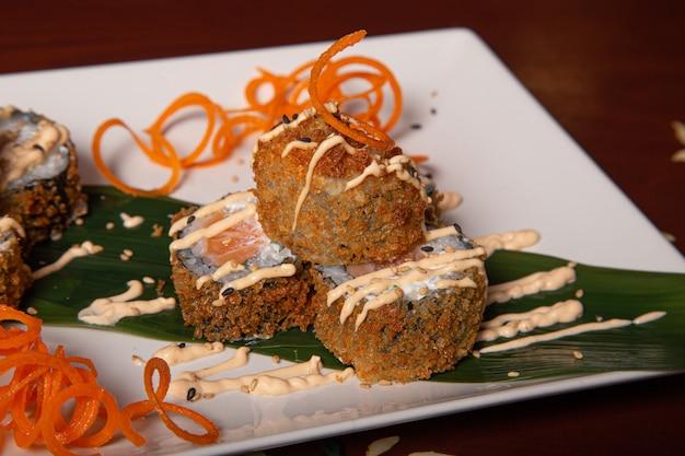 チーズ、玉ねぎ、サーモンの天ぷら巻きのクローズアップ。孤立した画像 Premium写真