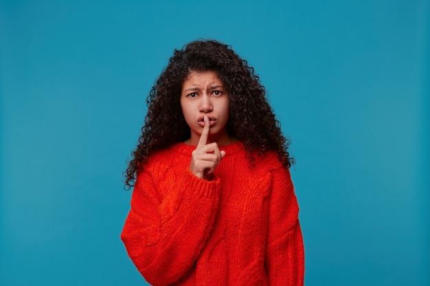 青い壁の上に孤立して立っている赤いセーターを着ているかなり怖い女性のクローズアップ 無料写真