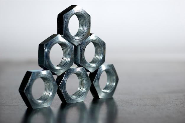 서로 옆에 벌집의 형태로 5 개의 크롬 금속 너트의 피라미드의 근접 프리미엄 사진
