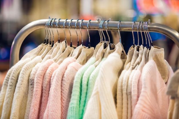 Крупный план рельса с вязаными свитерами в пастельных тонах Premium Фотографии