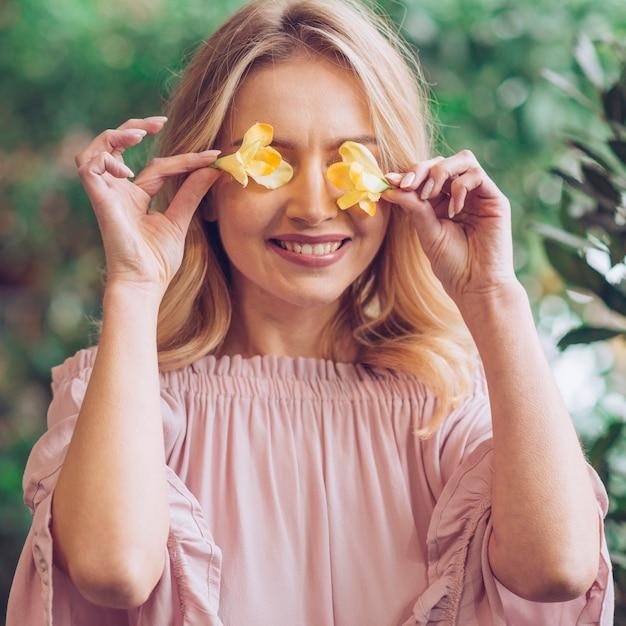 黄色のフリージアで彼女の目を覆っている笑顔の若い女性のクローズアップ 無料写真