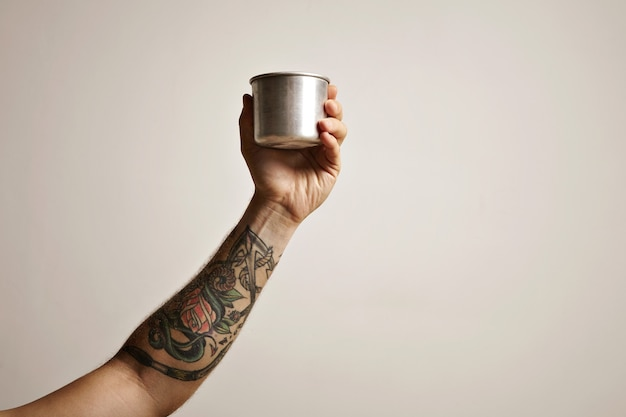 白い代替コーヒー醸造コマーシャルに鋼のトラベルカップで入れ墨の男の手のクローズアップ 無料写真