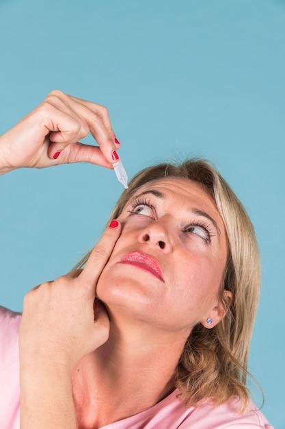 Крупный план женщины капает медицинские капли в ее глаз Premium Фотографии