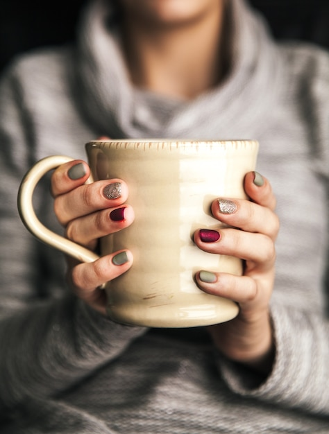 ホットコーヒーのカップを持っている女性の手のクローズアップ。ファッション、レジャー Premium写真