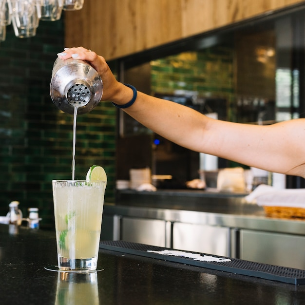 Close-up of a woman's hand making cocktail at bar counter Free Photo