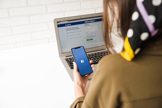 Close up of a woman trying to log in facebook application on mobile and laptop 23 2147844540