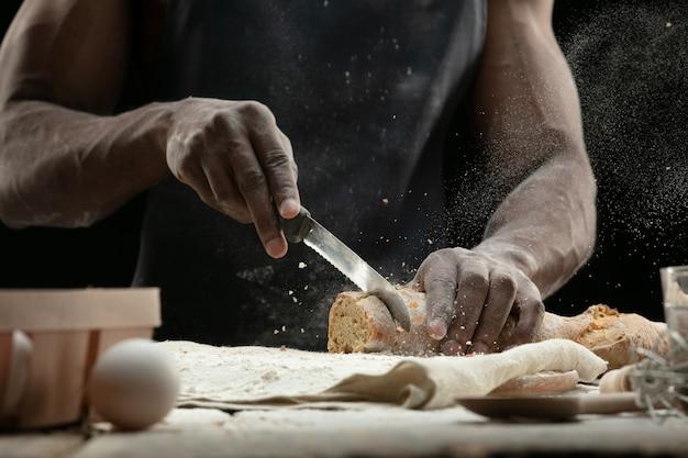Крупным планом афро-американский мужчина нарезает свежий хлеб кухонным ножом Бесплатные Фотографии