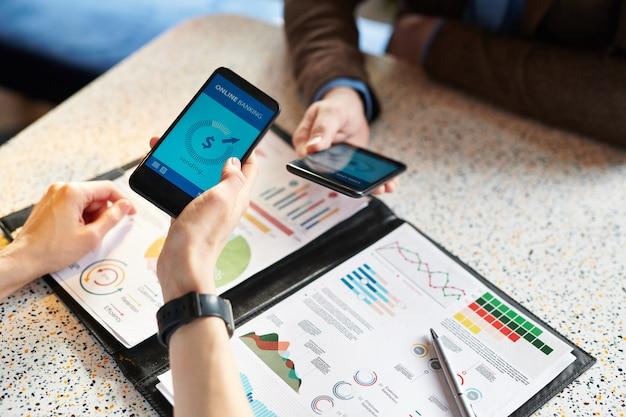 은행 모바일 앱을 통해 온라인 거래를하면서 차트 작업 및 스마트 폰을 사용하는 분석 전문가의 클로즈업 프리미엄 사진