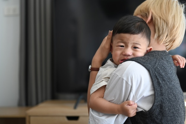 快適な家で泣いている赤ちゃんを抱いてアジアの母親のクローズアップ Premium写真
