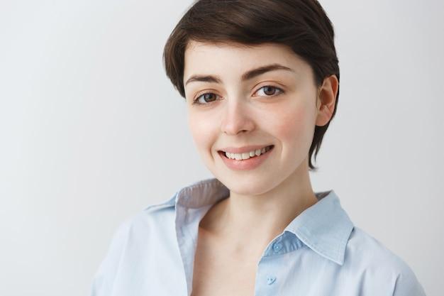 Крупный план привлекательной мечтательной женщины, смотрящей с обнадеживающей улыбкой Бесплатные Фотографии