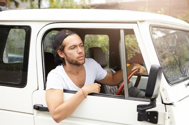 サファリ旅行中に極端な検索のために彼の白い車に座っているひげを持つ魅力的な若い男のクローズアップ。田舎道を運転するスナップバックの男性 無料写真