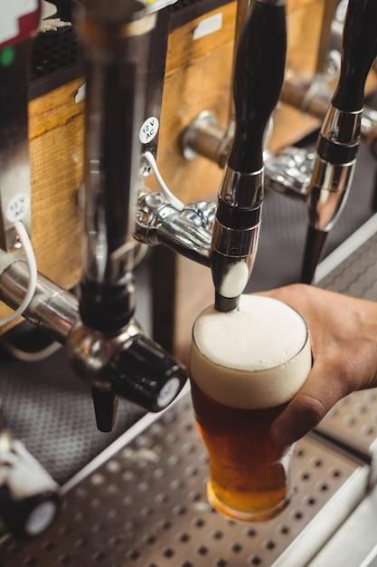 Крупный план барного тендера, разливающего пиво из барного насоса Бесплатные Фотографии