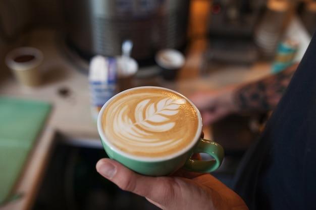芳香族カプチーノを保持しているバリスタのクローズアップ。コーヒーの販売の準備ができています。一杯のコーヒーを保持している男性の手。 Premium写真