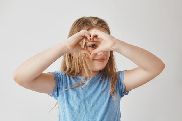그것을 통해보고, 미소와 행복 한 표정으로 사진을 위해 포즈를 취하는 손으로 하트를 만드는 아름 다운 금발 소녀 닫습니다. 무료 사진