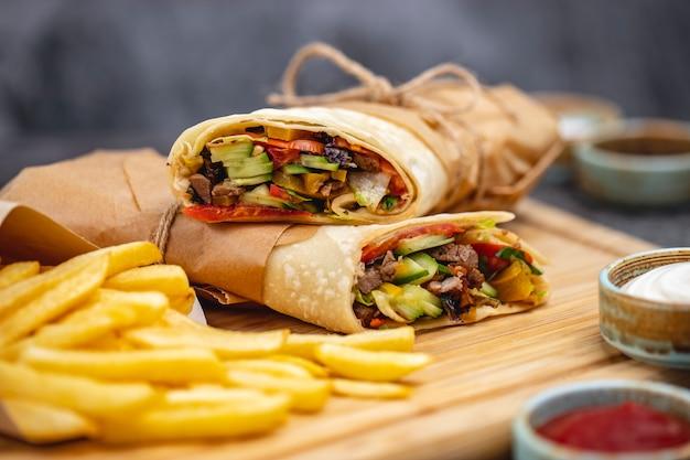 トマトキュウリレタスハラペーニョと牛肉のブリトーのクローズアップ、フライドポテトとソースを添えてください。 無料写真