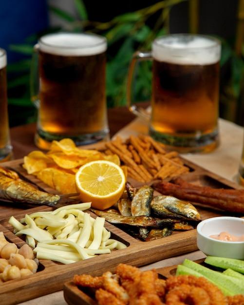 Крупный план пива закуски блюдо с сыром струнный копченая сельдь чипсы нута Бесплатные Фотографии