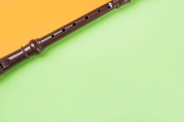 Крупный план блочной флейты на двойном оранжевом и зеленом фоне Бесплатные Фотографии