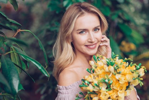 黄色の花の花束を持つ金髪の若い女性のクローズアップ 無料写真