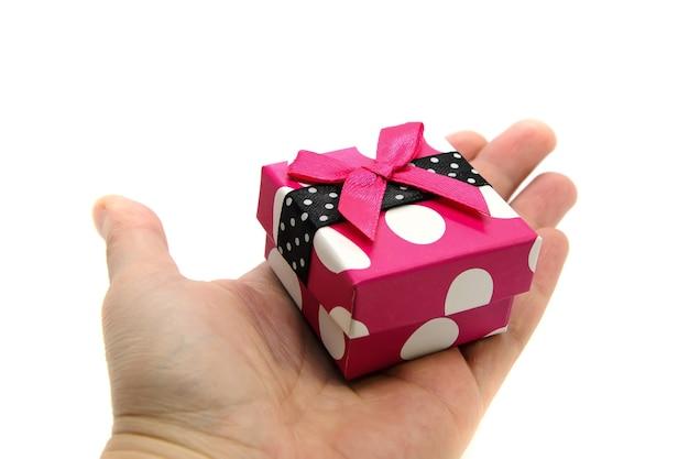 白い背景の上の手のひらに緋色のリボンと明るいピンクのギフトボックス白い水玉のクローズアップ Premium写真