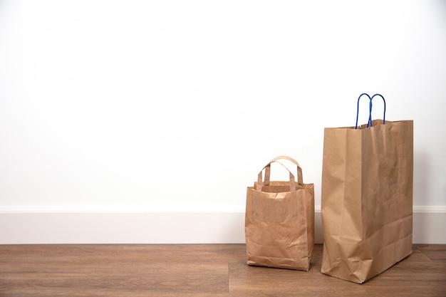 나무 바닥에 흰 벽, 텍스트에 대 한 복고풍 디자인 공간에 갈색 쇼핑백 닫습니다 프리미엄 사진