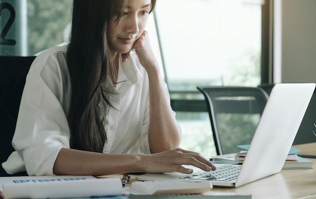 Крупным планом бизнес-леди или бухгалтер рука карандаш, работающий на калькуляторе, чтобы рассчитать отчет о финансовых данных, бухгалтерский документ и портативный компьютер в офисе, бизнес-концепция Premium Фотографии