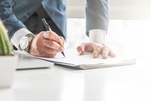 Крупным планом бизнесмена, писать на документ с ручкой на столе Premium Фотографии