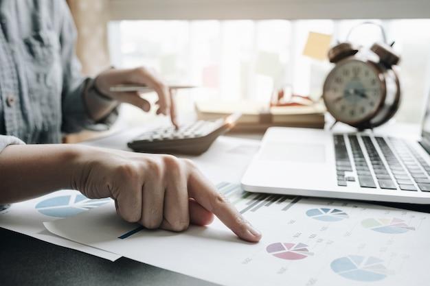 Закройте вверх ручки удерживания руки коммерсантки или бухгалтера работая на калькуляторе для того чтобы вычислить коммерческие данные Premium Фотографии