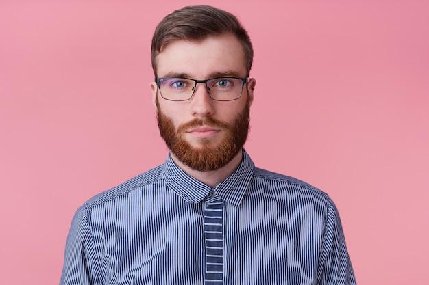 ピンクの背景に分離された感情のないカメラを見て、メガネで穏やかな感情のないひげを生やした若い男のクローズアップ。 無料写真