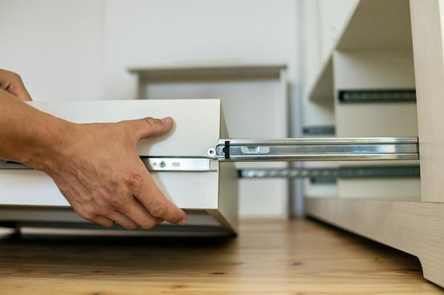현대 찬장 캐비닛에 슬라이딩 스키드에 나무 서랍을 설치하는 목수 손의 닫습니다. 프리미엄 사진
