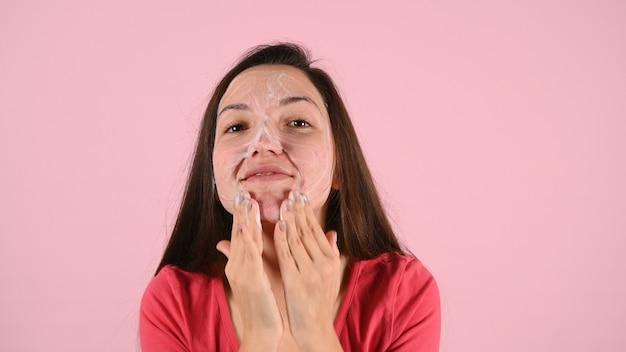 Крупным планом кавказская женщина, умывающая лицо, делая пузырьковую пену для лица и очищая кожу лица на розовом Premium Фотографии