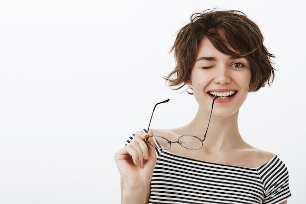 ふざけてウインクしてメガネの寺院を噛む生意気な笑顔の女性のクローズアップ 無料写真