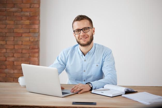 Закройте вверх жизнерадостного взрослого бородатого мужского менеджера в стеклах и классической рубашке сидя на столе в офисе, работающ на персональном компьютере, пишущ информацию в тетради. Бесплатные Фотографии