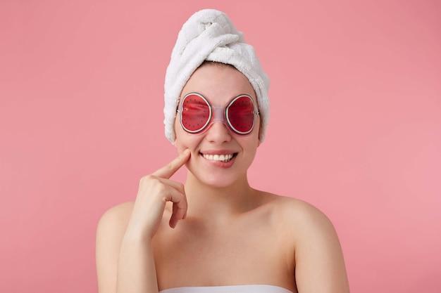 スパの後の陽気な若い女性のクローズアップ。頭にタオルをかけ、目のマスクを付け、広く笑顔で、とても幸せに感じ、頬に触れ、立っています。 無料写真