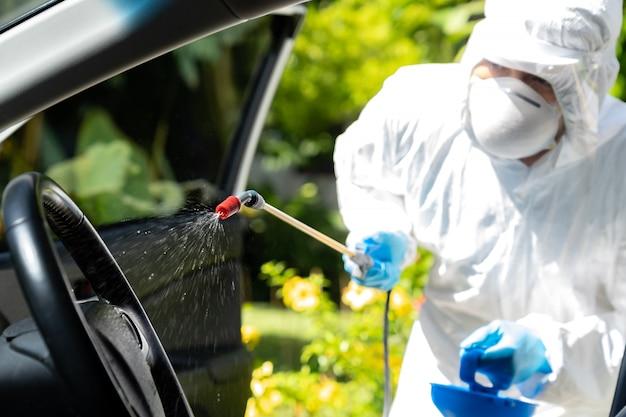 車内の化学アルコールスプレークリーニングのクローズアップ。コロナウイルスcovid-19を、個人用保護具ppeを装着した専門のクリーナーで消毒および汚染除去します。新しい通常の衛生概念。 Premium写真