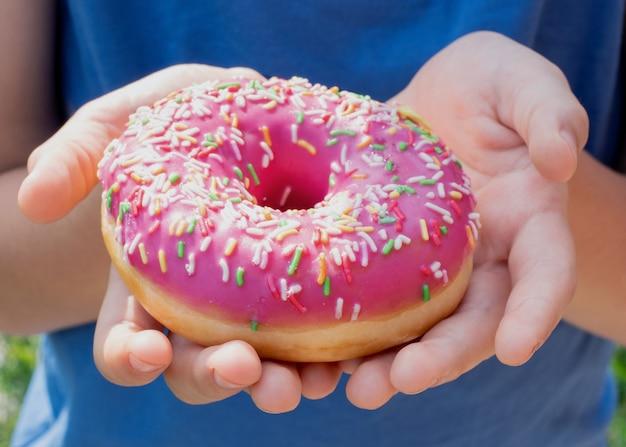 ピンクのアイシングと振りかけるドーナツを保持している子供の手のクローズアップ Premium写真