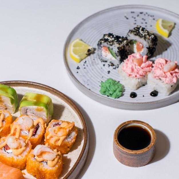 巻き寿司の一部を取っている箸のクローズアップ。軽いセラミックプレートの寿司セットロール Premium写真