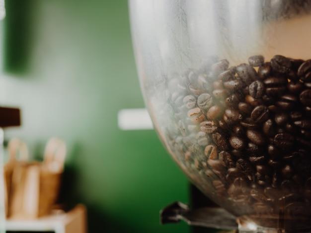 背景として緑の壁のマシンでコーヒー豆のを閉じます。 Premium写真