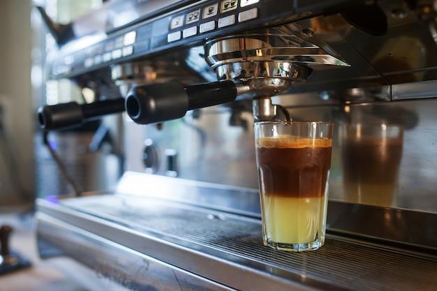 コーヒーマシンから注ぐコーヒーのクローズアップ。プロのコーヒー醸造 Premium写真
